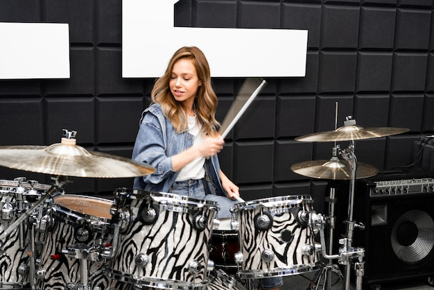 Creativity and music. young beautiful girl plays the drums. recording studio. musical equipment.