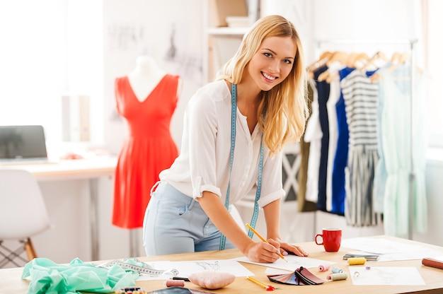 創造性は決して時代遅れになることはありません。ファッションワークショップで彼女の職場に寄りかかってカメラを描いて見ている若い女性の笑顔