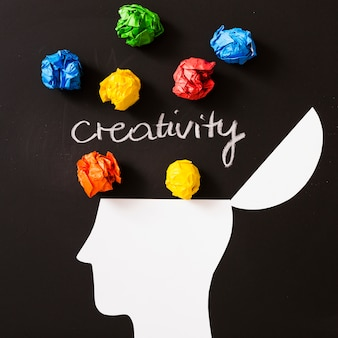 Creativity text with colorful crumpled paper ball over the open head against black background