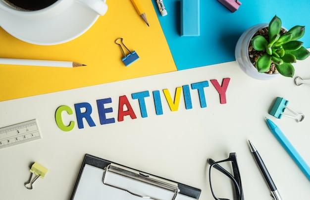 Слово творчества на фоне офиса стол с расходными материалами. красочный бизнес рабочий стол. концепции маркетинга