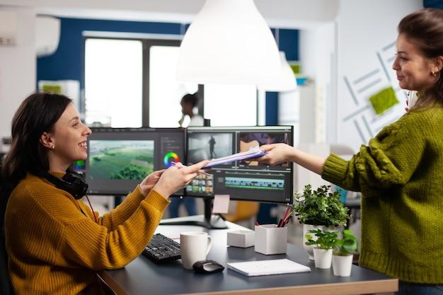 Creators drinking coffee and talking during office break sitting at desk in digital agency studio