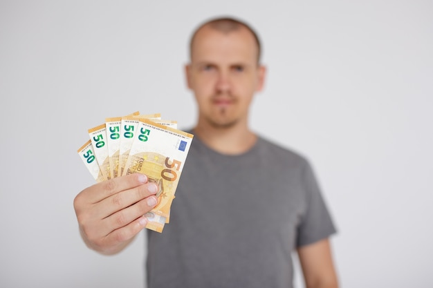 Credit, business and finance concept - close up of euro money banknotes in male hands over grey background