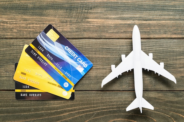Credit card and airplane model on wooden desk