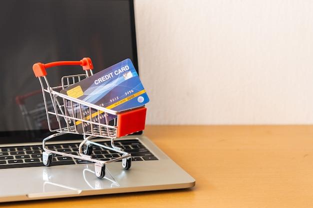 木のテーブルにクレジットカードとカートのスーパーマーケット。ショッピングコンセプト
