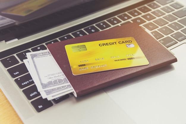 신용 카드와 여권 테이블에 노트북 컴퓨터 근처. 온라인 티켓 예약 개념