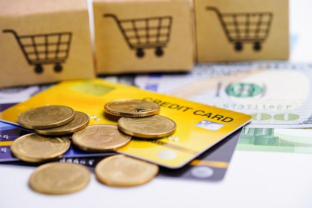 신용 카드 및 쇼핑 카트 상자와 동전 미국 달러 지폐.