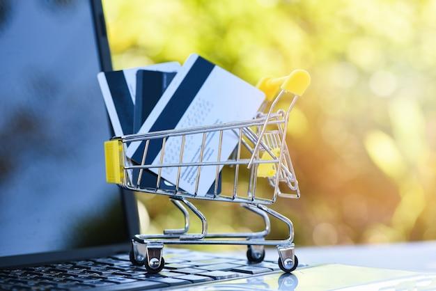 クレジットカードとラップトップの簡単な支払いオンラインショッピングの概念を使用してオンラインショッピングのためのクレジットカードとデビットカードのショッピングカート