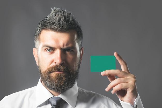 手に空白の名刺を持つ安全なオンライン支払いハンサムな男としてのクレジットカードビジネスマン