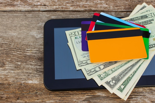Credit card, dollars, computer tablet on wood