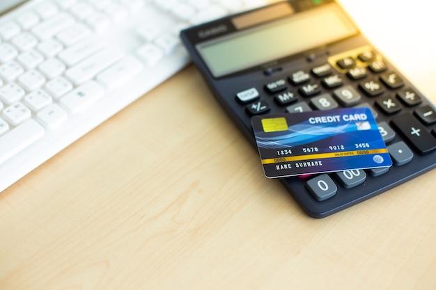 나무 테이블에 검은 계산기로 지불을 위한 신용 카드. 텍스트 디자인을 위한 복사 공간