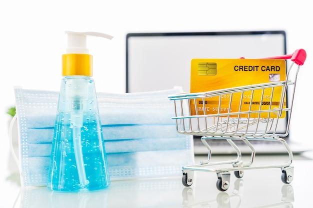 손 소독제 및 수술 용 마스크 온라인 쇼핑이있는 노트북 화면의 신용 카드 앞면, covid-19 전염병에 대한 가정 개념의 검역 작업
