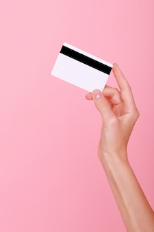 Credit card in hand on pink background