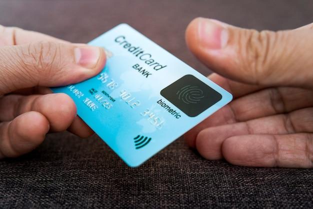 Кредитная карта имеет встроенный сканер отпечатков пальцев. иллюстрация биометрической безопасности платежей. одна мужская рука держит синюю карточку, а другая трогает сканер большим пальцем. проверка нажатием. личность.