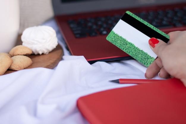 Кредитная карта в руке возле клавиатуры красного ноутбука