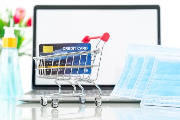 サージカルマスクが付いているラップトップ画面のショッピングカートの前面にあるクレジットカード