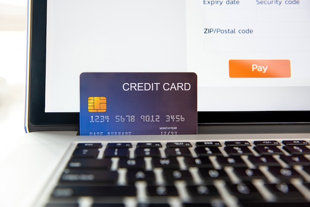 Credit card on laptop computer representing online payment