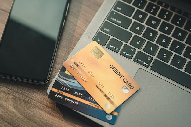 Credit card of laptop computer,smartphone and coffee cup on wooden background,online banking concept