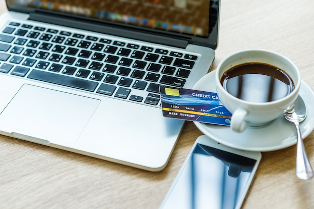 Credit card and laptop computer with smartphone and coffee cup on wooden background