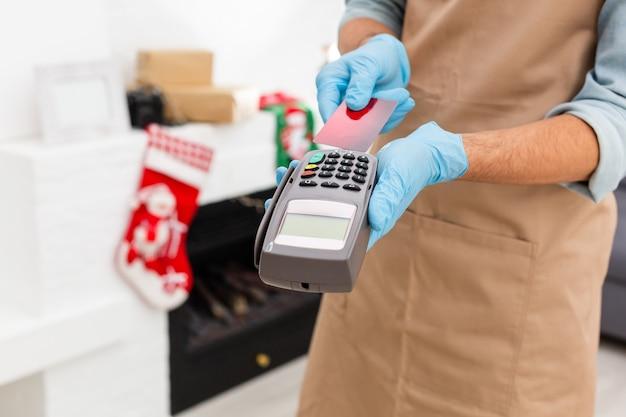 돈 거래를 위한 신용 카드 기계. 신용 카드로 장갑을 끼고 pos 터미널을 통해 스와이프하고 핀 코드를 입력합니다. 전자 화폐의 뱅킹 서비스. 재정적 성공과 안전