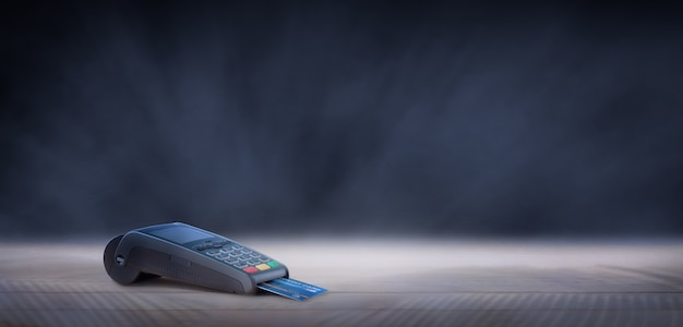 어두운 배경에서 나무에 신용 카드 기계입니다. 블랙 프라이데이 판매 개념