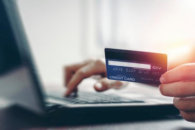 ノートパソコンでオンライン決済やインターネットショッピングを行うクレジットカード。
