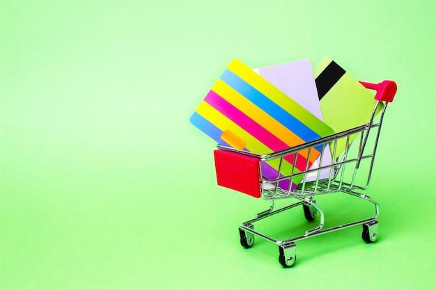다양한 색상의 신용 카드 모형은 노란색 배경의 빨간색 쇼핑 카트에 배치됩니다.