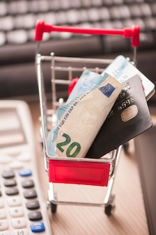 Credit card and money within shopping cart