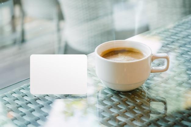 コーヒーカップの近くのクレジットカード