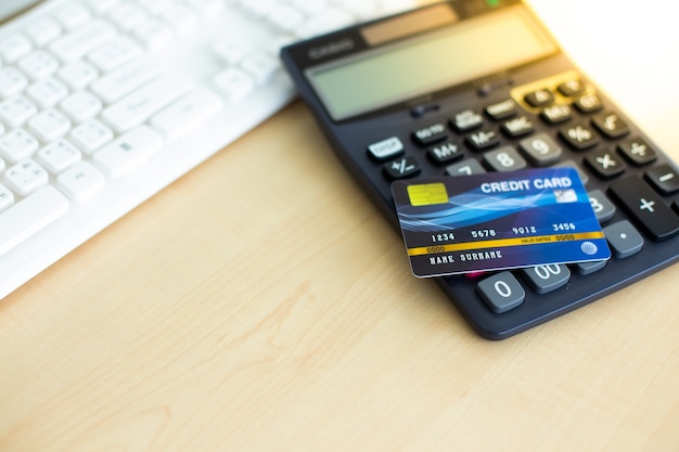 Credit card for pay with black calculator on wood table. copy space for text disign