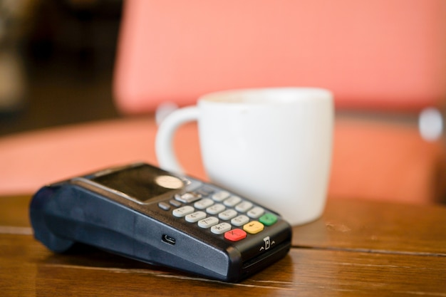 Credit card payment machine with white coffee cup on table in the cafe