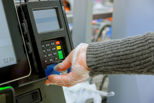 Credit card payment terminal in shop on human hand in gloves respecting health standards of coronavirus covid-19
