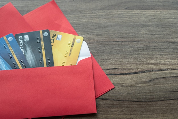Credit card in red envelope for chinese new year festival bonus on wooden table background.