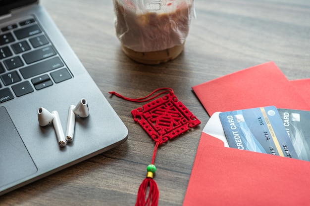 Credit card in red envelope, earphone on laptop computer with the chinese text blessings written on it is a spring with coffee isolate on wooden background office desk for chinese new year bonus