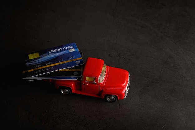 The credit card on the red pickup model on the black floor