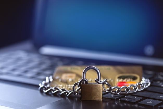 신용카드 보안, 안전한 거래. 노트북 근처에 자물쇠와 체인으로 닫힌 신용 카드.
