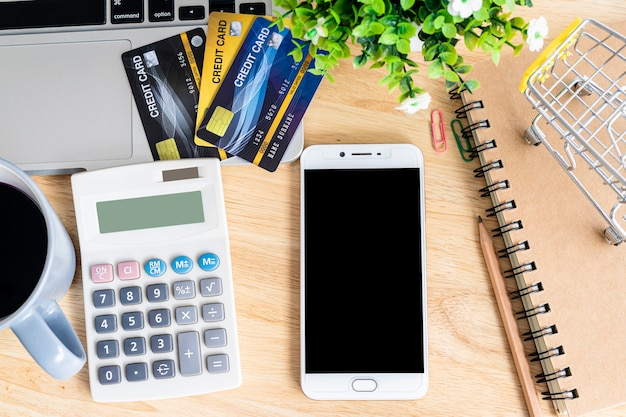 Credit card in shopping cart with laptop,notebook,flower pot tree,smartphone and calculator on wooden background, online banking top view office table.