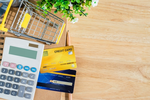 Credit card in shopping cart with notebook and calculator