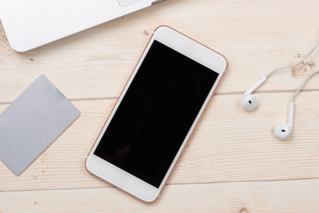 얕은 피사계 심도가 있는 현대적인 작업 공간의 데스크탑 컴퓨터 옆에 있는 스마트폰에 있는 신용 카드