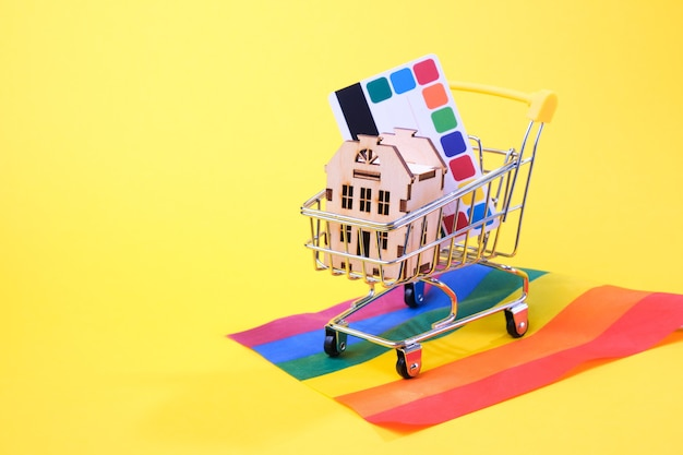 Credit card and a small house in a shopping cart on the flag of the lgbt community, yellow background, copy place