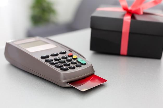 나무 테이블 배경에 신용 카드 단말기, 카드 및 선물