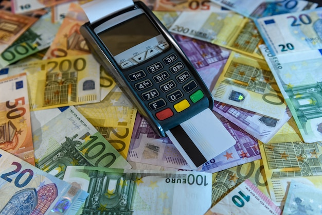 Credit card in terminal over euro banknotes