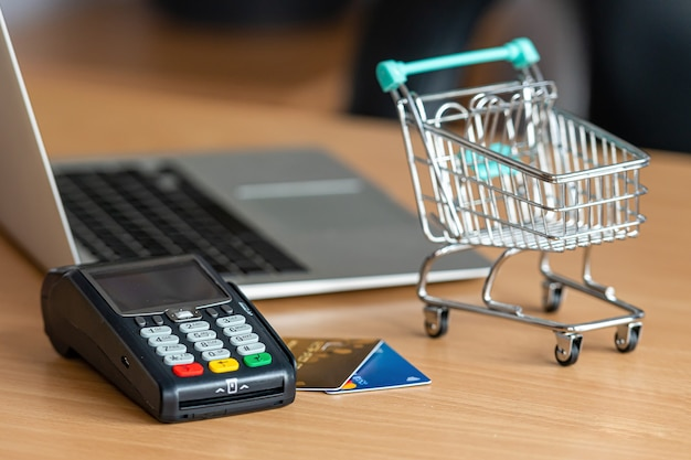 Credit card terminal on table in the store with credit card, laptop and mini shopping cart