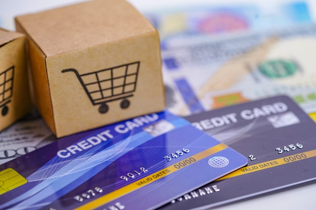 Credit card and us dollar banknotes with shopping cart box.