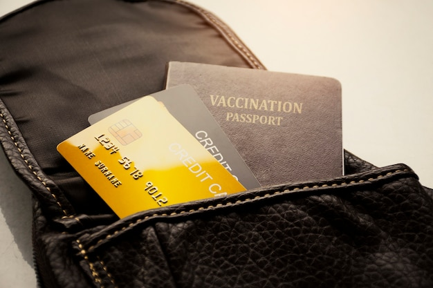 Credit card and vaccination passport for international travel in leather bag
