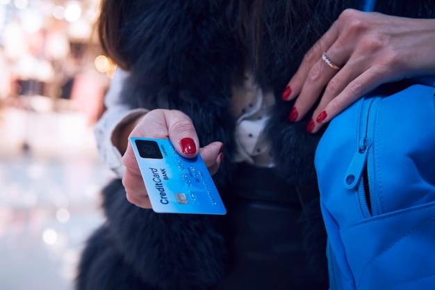 젊은 여성의 손에 생체 인식 시스템이 있는 신용 카드. 쇼핑 센터에서 카드로 지불할 것을 제안하는 빨간 매니큐어를 한 여성의 반신 사진. 갈색 머리는 신용 돈을 사용하여 부티크에서 물건을 구매합니다.