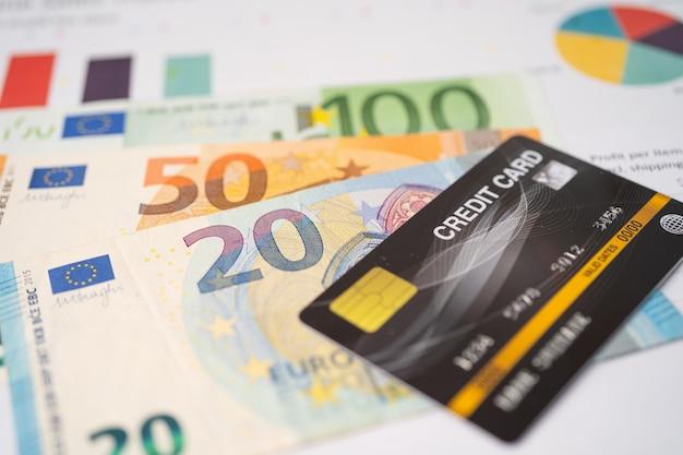 Кредитная карта с банкнотами евро на миллиметровой бумаге.
