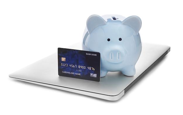 貯金箱とラップトップが分離されたクレジットカード。オンラインバンキングの概念