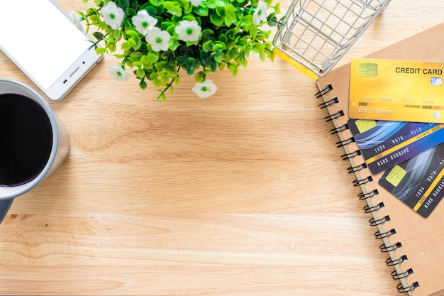 Credit cards,notebook,flower pot tree,smartphone,shopping cart and coffee cup on wooden background,online banking top view office table.