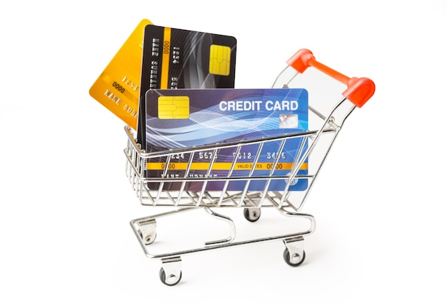 Credit cards in shopping cart isolated on white surface. .