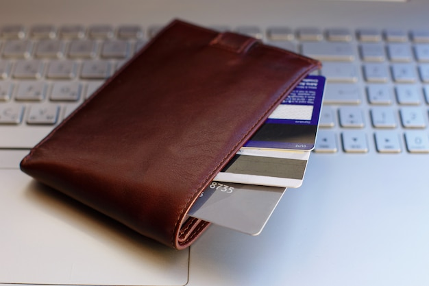 Credit cards in the wallet on the laptop keyboard.